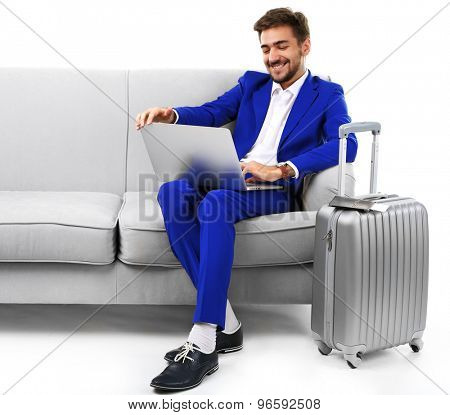 Business man with suitcase and laptop sitting on sofa isolated on white