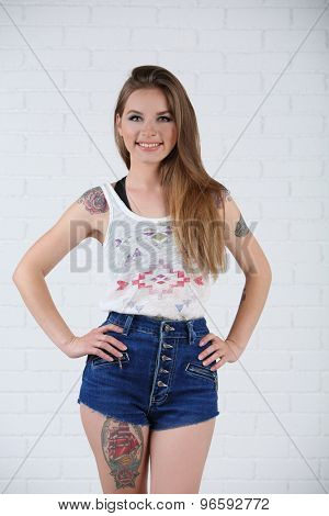 Beautiful girl with stylish make-up and tattooed body on light background