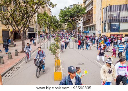 Unidentified hispanic pedestrians and cyclists moving through city street Candelaria area Bogota