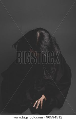 gothic dark woman with large black cloth on gray background, Sadness