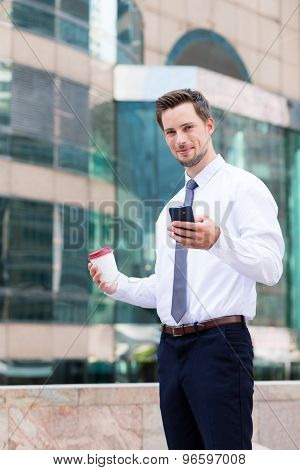 Caucasian businessman holding with coffee and cellphone at outdoor