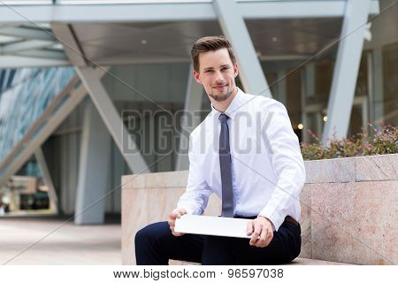 Caucasian businessman sitting at outdoor and hld with laptop computer