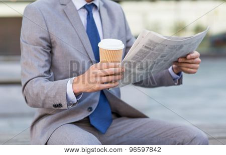 business, news, break and people and concept - close up of businessman reading newspaper and drinking coffee from paper cup over office building