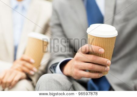 business, hot drinks and people concept - close up of business people hands with coffee cups