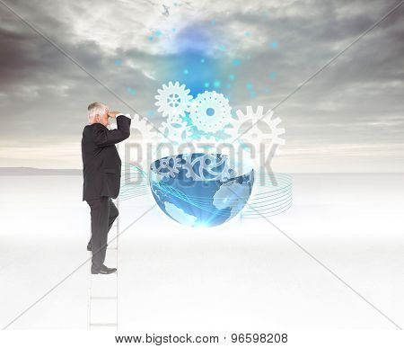 Mature businessman standing on ladder against grey sky