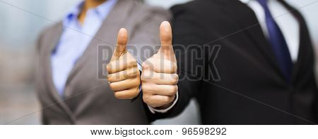 business and office concept - businessman and businesswoman showing thumbs up in office