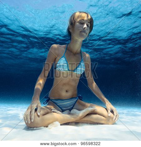 Skinny lady relaxing in lotus pose underwater on the sandy bottom of a tropical sea