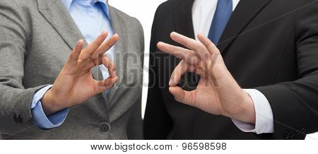 business and office concept - smiling businessman and businesswoman showing ok sign