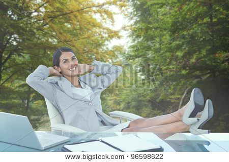 Businesswoman relaxing in a swivel chair against scenic shot of narrow road along forest