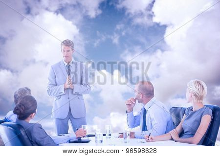 Business people listening during meeting against blue sky with white clouds