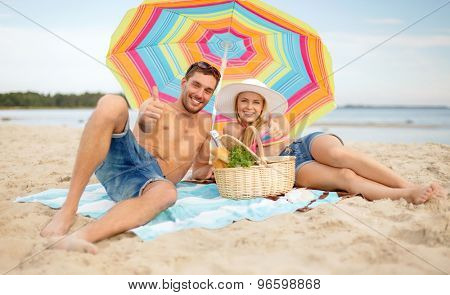 summer, holidays, vacation and happy people concept - happy couple with picnic basket and parasol showing thumbs up on beach