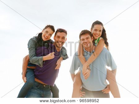 summer holidays, tourism, travel, relations and people concept - group of happy friends having fun outdoors