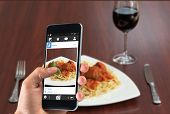 picture of meatball  - hand holding smartphone against front view of spaghetti and meatballs with red wine - JPG