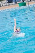 stock photo of crawl  - Young girl in goggles and cap swimming back crawl stroke style in the blue water pool - JPG