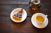 foto of teapot  - The slice of vegetarian nut pie on a white plate lies on a dark wooden background - JPG