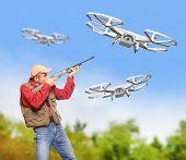 stock photo of shotgun  - Man with shotgun shooting down drone flying over his farm - JPG