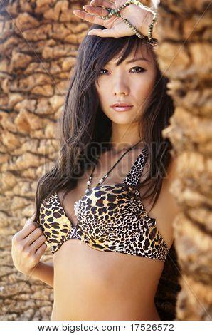 Beautiful Asian woman in tropical setting wearing leopard print bra bikini