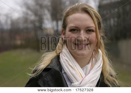 Norwegian girl smiling into the camera in a park wearing a scarf and a black jacket.