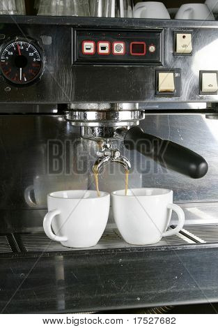 Detail image of two cups of espresso being made in an industrial profesional machine