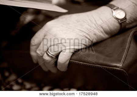 A detail of an old womans hand on her purse using shallow depth of field. The image is given a slight sepia toning