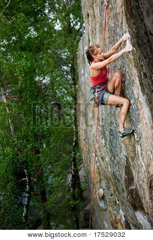An eager female climber on a steep rock face looks for the next hold. Shallow depth of field is used to isolated the climber with the focus on the head.