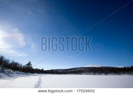 A ski trail going accross a frozen lake infront of a mountain landscape