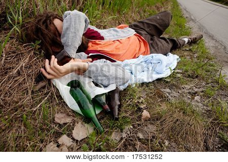 A drunk homeless man laying the ditch