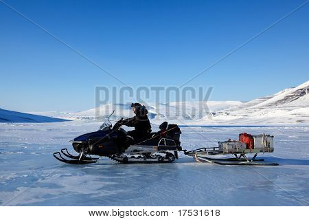 A man on a snowmobile against a winter landscape