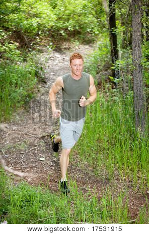 Portrait of handsome man running in forest against blur background