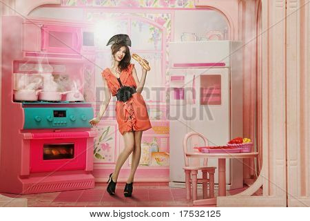 Pretty woman as a doll in the kitchen