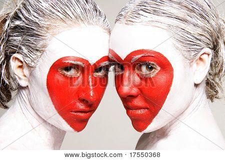 Zwei Mädchen mit bemalten Gesichtern liefern rote Herz-Muster