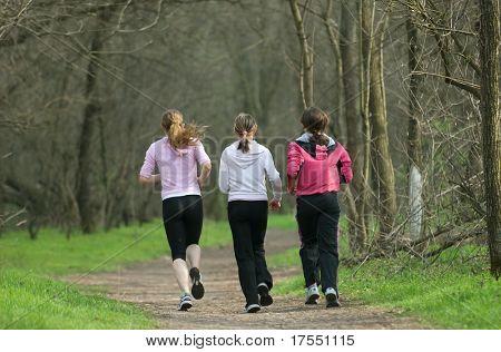 Three girls running trough the park