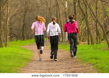 Three girls running through the park