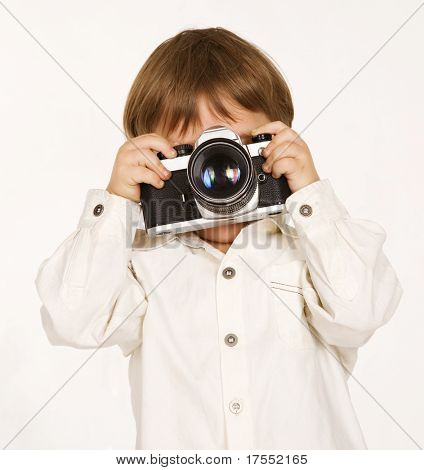Pretty boy shooting with camera over white