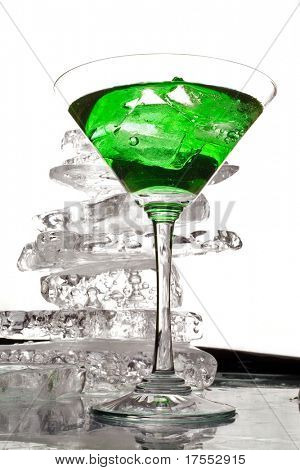 Wineglass with green liquor an a pile of clear ice