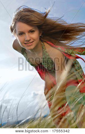 Rubia natural en prado verde con pelo volando
