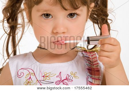 Adorable little girl applying make-up with lipstick
