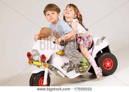Adorable boy and little girl sitting on white toy bike