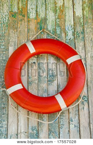 Red life buoy on wooden wall background