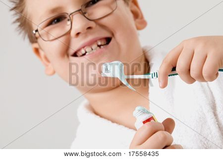 Funny young boy cleaning teeth