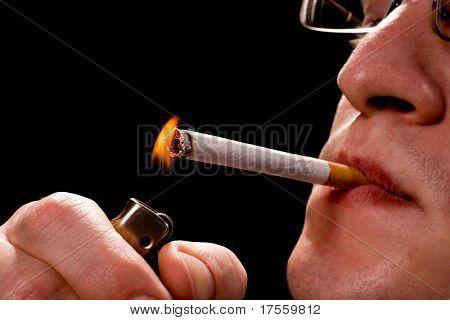 Mann zündet sich eine Zigarette über schwarz