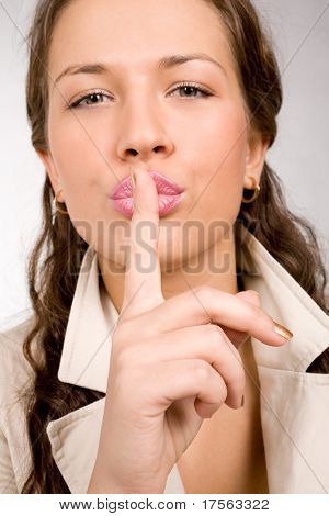 Perfect young woman making a silence sign