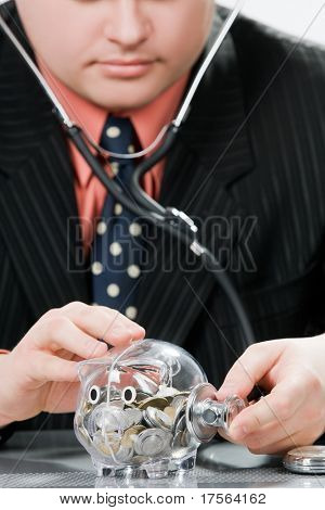 Businessman checking piggy bank health with stethoscope