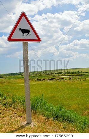 Cattle crossing warning sing with cow corral on far background