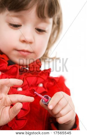 Pretty little girl in red applying polish on nails
