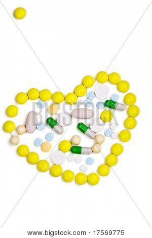 Various color tablets and capsules in the shape of a heart on white background