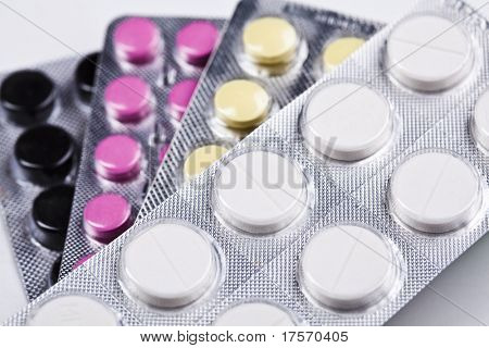 Stack of packs of white, yellow, black and red pills, abstract medical background