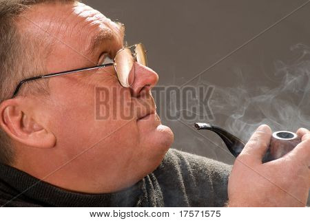 Mid aged man dreaming with smoking pipe in hand