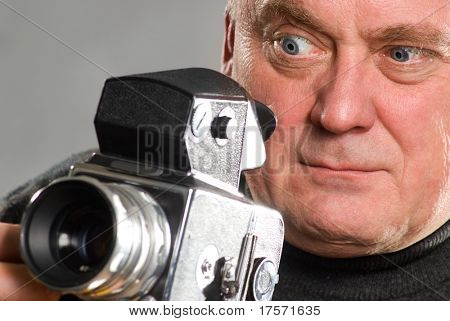Photographer staring into old camera viewfinder