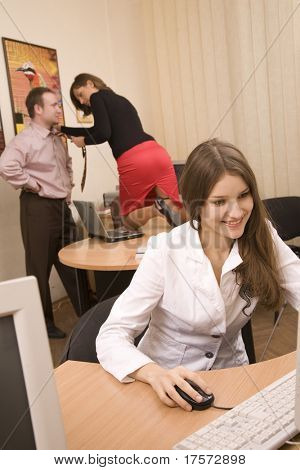 Pretty smiling girl at office and  her colleagues flirting on background